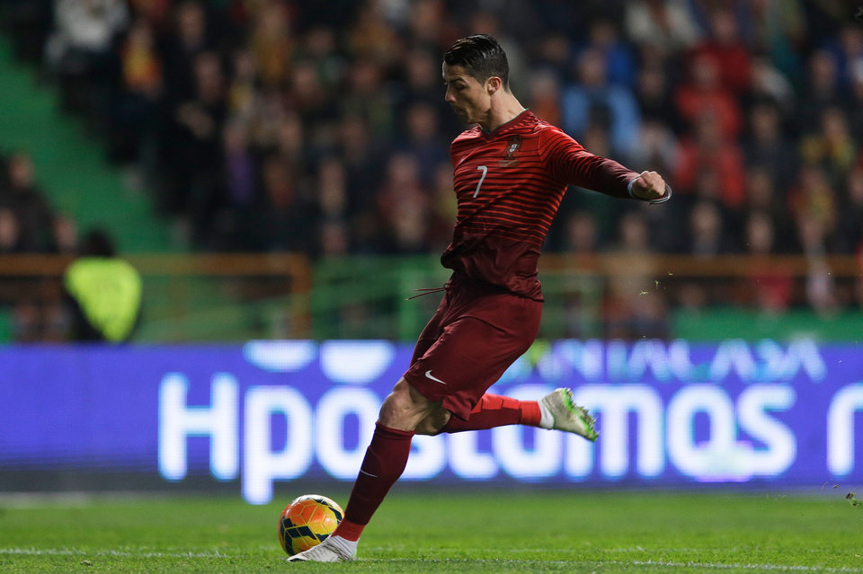 Photo - Portugal's Cristiano Ronaldo shoots to score the opening goal during their friendly soccer match with Cameroon Wednesday, March 5 2014, in Leiria, Portugal. It was Ronaldo's 48th goal with Portugal making him the national team's best scorer ever. (AP Photo/Armando Franca)