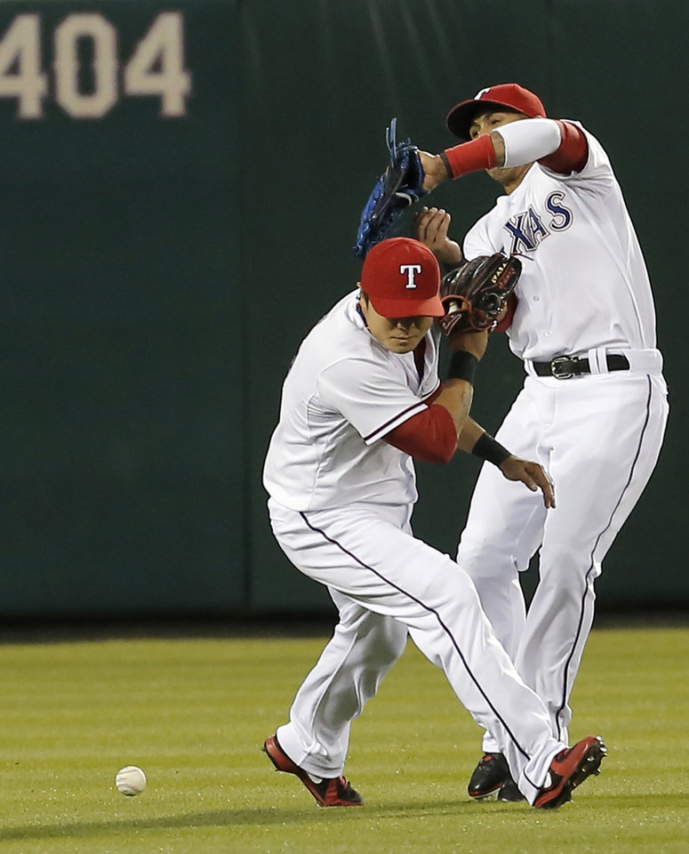 Photo - Texas Rangers center fielder Leonys Martin, right, and left fielder Shin-Soo Choo (17) are unable to catch a pop fly hit by Seattle Mariners' Mike Zunino during the fourth inning of a baseball game on Wednesday, April 16, 2014, in Arlington, Texas. (AP Photo/Brandon Wade)