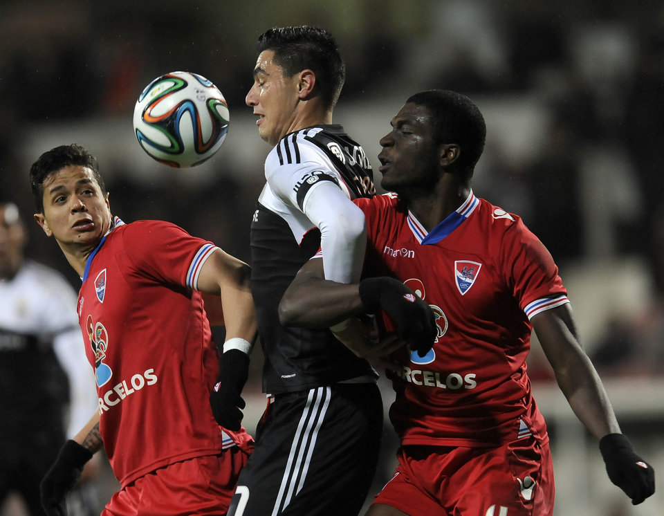 Photo - Benfica's Oscar Cardozo, from Paraguay, eyes the ball with Gil Vicente's Halisson Santos, right, and Luan Scapolan, both from Brazil, in a Portuguese League soccer match at the Cidade de Barcelos stadium, in Barcelos, northern Portugal, Saturday, Feb. 1, 2014. Cardozo failed to score a penalty in Benfica's 1-1 draw.(AP Photo/Paulo Duarte)