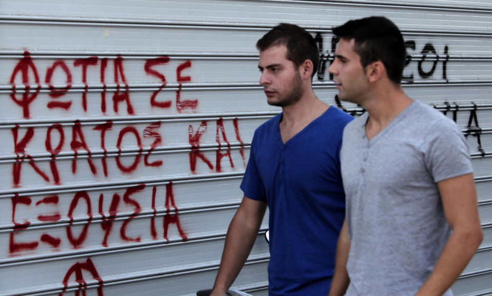 Photo -   Pedestrian walk in front of graffiti in Athens, Tuesday, Sept. 25, 2012. Unions have called a nationwide general strike Wednesday to protest new austerity measures being hammered out between the government and Greece's international creditors to ensure the country continues receiving emergency loans that have kept it afloat since 2010. Graffiti reads