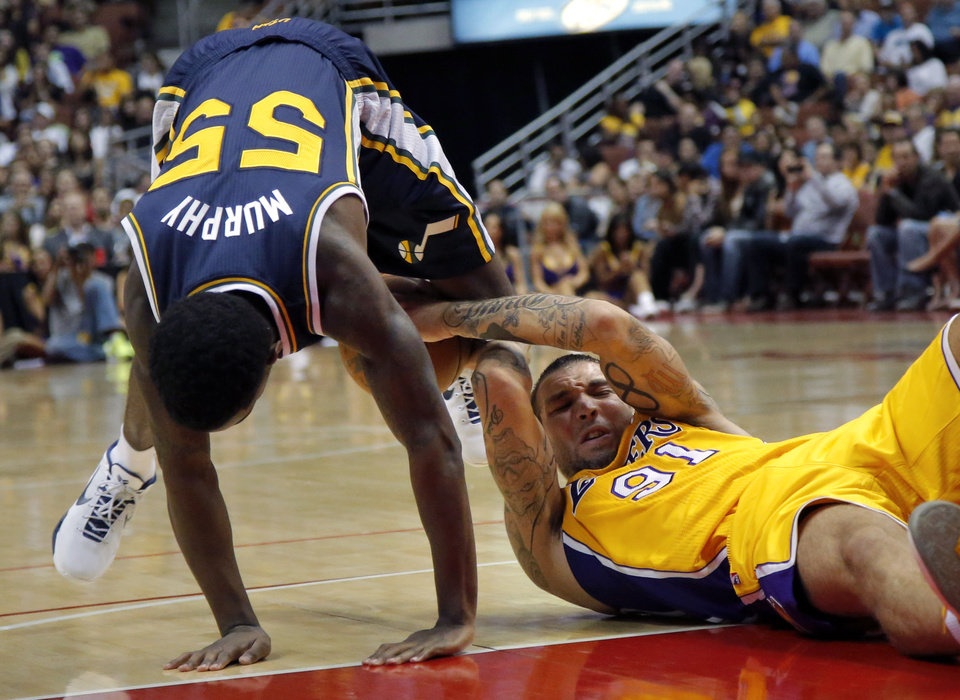 Photo -   Los Angeles Lakers' Reeves Nelson, right, and Utah Jazz's Kevin Murphy fight for the ball during the first half of an NBA preseason basketball game in Anaheim, Calif., Tuesday, Oct. 16, 2012. (AP Photo/Jae Hong)