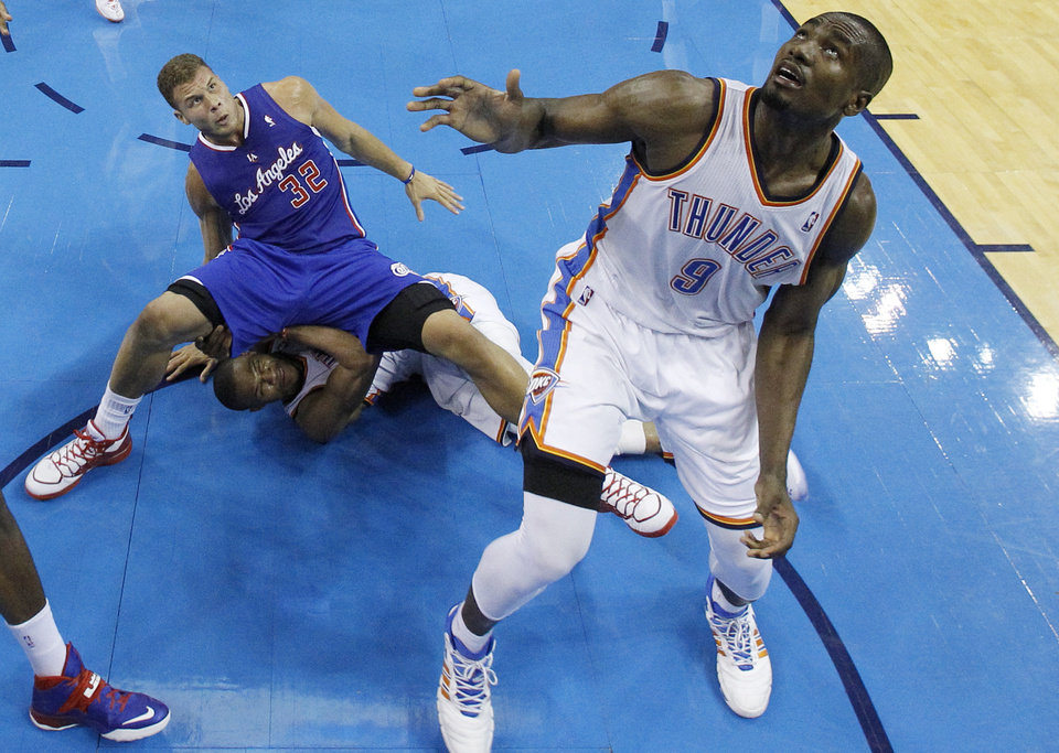 Photo - Los Angeles Clippers forward Blake Griffin (32) falls on top of Oklahoma City Thunder guard Russell Westbrook (0) as forward Serge Ibaka (9) watches for a rebound in the third quarter of Game 1 of the Western Conference semifinal NBA basketball playoff series in Oklahoma City, Monday, May 5, 2014. Los Angeles won 122-105. (AP Photo/Sue Ogrocki)