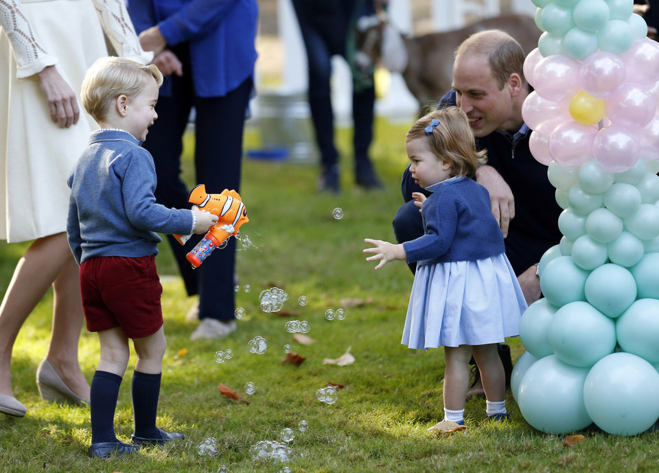 Photo - Britain's Prince William and Princess Charlotte look on as Prince George plays with a bubble gun at a children's party at Government House in Victoria, British Columbia, Thursday, Sept. 29, 2016. (Chris Wattie/The Canadian Press via AP, Pool)