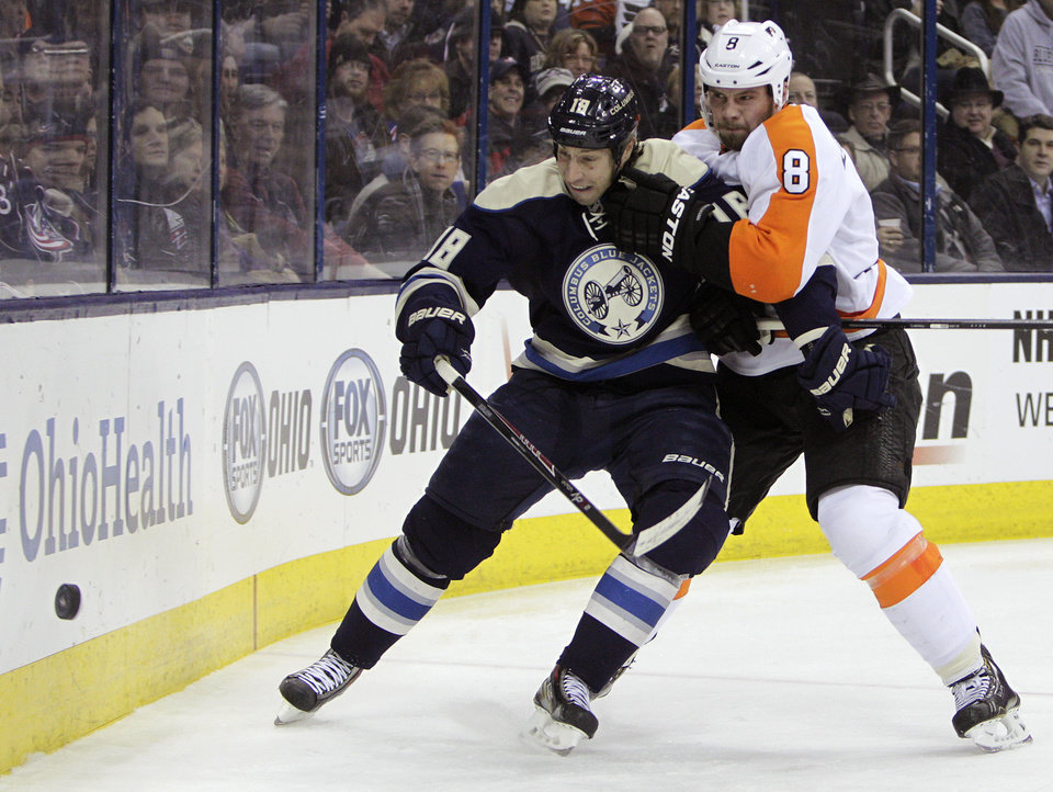 Photo - Philadelphia Flyers' Nicklas Grossman, right, of Sweden, and Columbus Blue Jackets' RJ Umberger fight for a loose puck during the second period of an NHL hockey game Thursday, Jan. 23, 2014, in Columbus, Ohio. (AP Photo/Jay LaPrete)