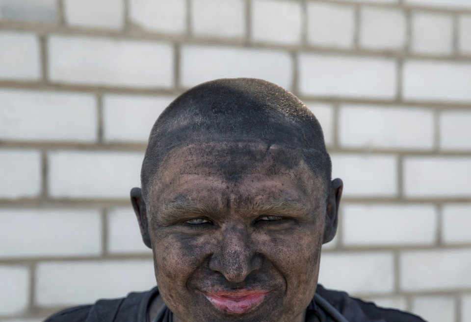 Photo - In this picture taken on Tuesday, May 20, 2014, a Ukrainian miner smiles after drinking water at a mine in Donetsk, Ukraine. In the roiling debate over eastern Ukraine, where pro-Russian separatist attacks have turned increasingly bloody, neither the country's richest man nor some of his dirt-poor compatriots have much time for patriotism, ethnic feuding or political parties. (AP Photo/Vadim Ghirda)