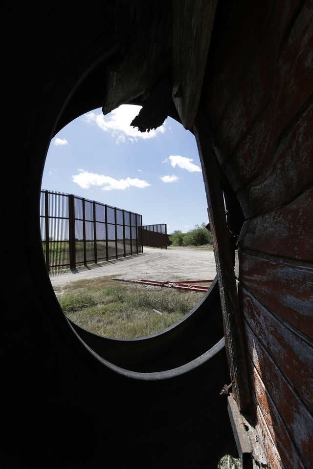 "This Sept. 6, 2012, photo shows the U.S.-Mexico border fence that passes through the cotton farm of Teofilo ""Junior"" through an old tractor tire in Brownsville, Texas. Since 2008, hundreds of landowners on the border have sought fair prices for property that was condemned to make way for the fence, but many of them received initial offers that were far below market value. (AP Photo/Eric Gay)"