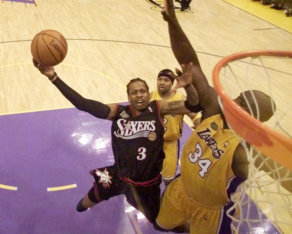 Photo - BASKETBALL CHAMPIONSHIP: Philadelphia 76ers player Allen Iverson, left, goes up against Los Angeles Lakers player Shaquille O'Neal, right, as teammate Derek Fisher looks on at rear in the third quarter of Game 1 of the NBA Finals in Los Angeles, Wednesday, June 6, 2001. (AP Photo/Pool, Jeff Mitchell)
