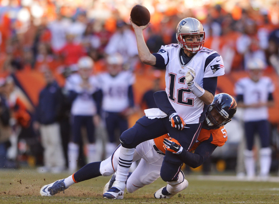 Photo - New England Patriots quarterback Tom Brady (12) is hauled to the turf by Denver Broncos defensive end Jeremy Mincey (57) during the second half of the AFC Championship NFL playoff football game in Denver, Sunday, Jan. 19, 2014. (AP Photo/Jack Dempsey)