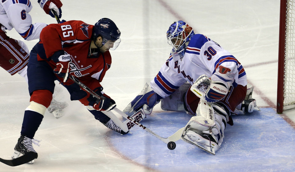 Photo - New York Rangers goalie Henrik Lundqvist (30), from Sweden, makes a save on a shot by Washington Capitals center Mathieu Perreault (85) in overtime of Game 5 first-round NHL Stanley Cup playoff hockey series, Friday, May 10, 2013, in Washington. The Capitals won 2-1, in overtime. (AP Photo/Alex Brandon)