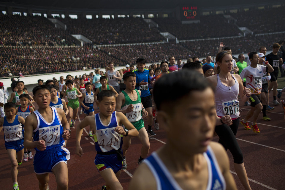 Photo - Runners take off from the starting line inside Kim Il Sung Stadium at the beginning of the  Mangyongdae Prize International Marathon in Pyongyang, North Korea on Sunday, April 13, 2014. The annual race, which includes a full marathon, a half marathon, and a 10-kilometer run, was open to foreign tourists for the first time this year. (AP Photo/David Guttenfelder)
