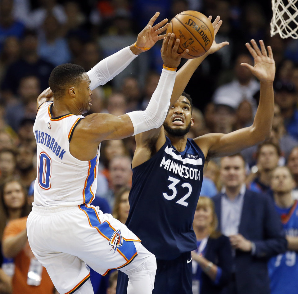 Photo - Oklahoma City's Russell Westbrook (0) passes as Minnesota's Karl-Anthony Towns (32) defends during an NBA basketball game between the Oklahoma City Thunder and the Minnesota Timberwolves at Chesapeake Energy Arena in Oklahoma City, Sunday, Oct. 22, 2017. Minnesota won 115-113. Photo by Nate Billings, The Oklahoman