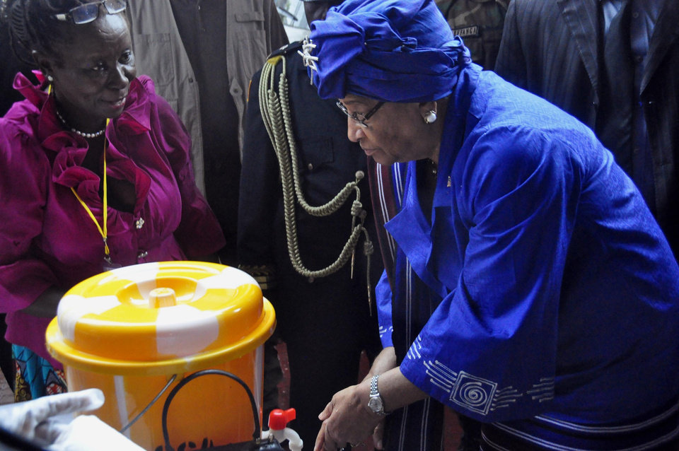 Photo - In this photo taken on Saturday, July 26, 2014, Liberia President  Ellen Johnson Sirleaf, right, demonstrates to people how to wash their hands properly in order to prevent the spread of the Ebola virus, during  Independence Day celebrations in the city of Monrovia, Liberia. Scientists from Fort Detrick say the number of Ebola cases in West Africa is much larger than official estimates indicate. Researchers from the U.S. Army Medical Research Institute of Infectious Diseases, who have worked in Sierra Leone and Liberia, say the current outbreak reaches beyond the 1,200 confirmed, suspected or probable cases and over 600 deaths that the World Health Organization has identified in West Africa as of July 23. (AP Photo/Abbas Dulleh)