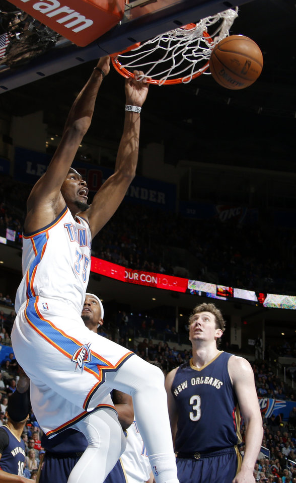 Photo - Oklahoma City's Kevin Durant (35) dunks the ball as New Orleans' Omer Asik (3) watches during an NBA game between the Oklahoma City Thunder and the New Orleans Pelicans at Chesapeake Energy Arena on Friday, Feb. 6, 2015. Photo by Bryan Terry, The Oklahoman