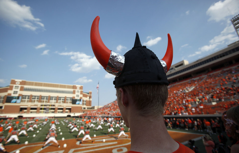 Photo - Fan Mark Denker watches the Oklahoma State football team warm up prior to the Cowboys game vs. Louisiana-Lafayette at Boone Pickens Stadium in Stillwater, Okla., Saturday, Sept. 3, 2011. Photo by Sarah Phipps, The Oklahoman