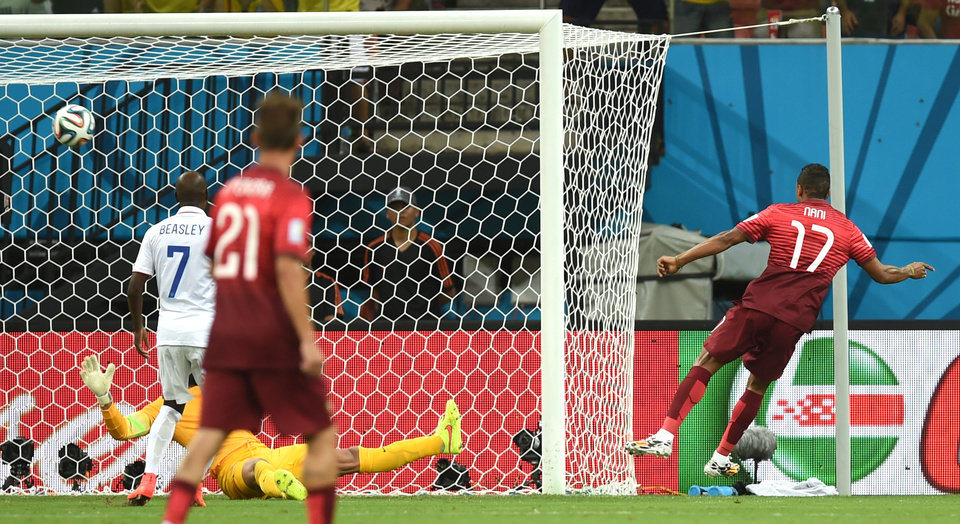 Photo - Portugal's Nani, right, scores the opening goal during the group G World Cup soccer match between the USA and Portugal at the Arena da Amazonia in Manaus, Brazil, Sunday, June 22, 2014. (AP Photo/Paulo Duarte)