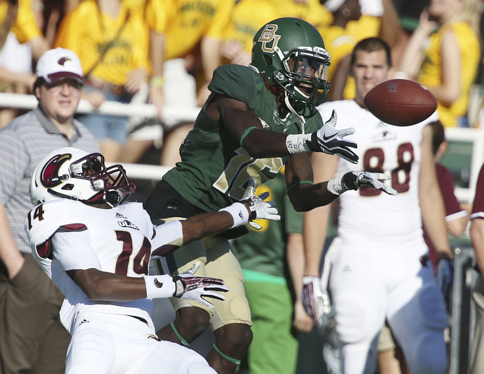 Photo - Baylor wide receiver Tevin Reese (16) pulls in a pass over Louisiana-Monroe cornerback Vincent Eddie, left, during an NCAA college football game, Saturday, Sept. 21, 2013, in Waco, Texas. (AP Photo/Waco Tribune Herald, Rod Aydelotte)