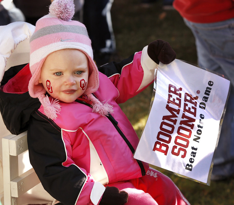 Photo - Twenty-month-old Lexie Lorton holds a sign supporting the Oklahoma Sooners while sitting in a small covered wagon pulled by her dad, Jay Lorton. The Lortons live in Tulsa.  ESPN broadcast their weekly pre-game sports show, GameDay,  from the  the campus of the University of Oklahoma, Saturday morning, Oct. 27, 2012. The network's broadcast crew is in Norman for the OU - Notre Dame football game Saturday night.  Several thousand OU fans and a smattering of Notre Dame supporters , many carrying homemade signs, crowded around the stage to watch the live broadcast.  Photo by Jim Beckel, The Oklahoman
