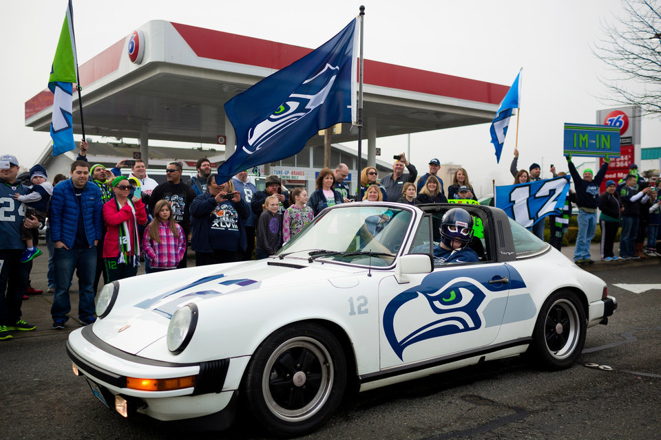 Photo - Kel Klink, in his vinyl-wrapped 1978 Porsche 911, rallies alongside thousands of diehard 12thMan fans who lined South 188th Street to see off the Seahawks team buses on their way to the airport en route to New York for Super Bowl XLVIII, Sunday, Jan. 26, 2014, in SeaTac, Wash. (AP Photo/seattlepi.com, Jordan Stead)