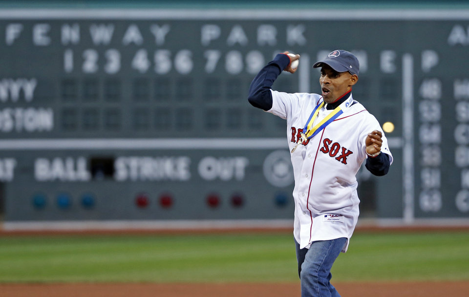 Photo - Meb Keflezighi, men's winner of the Boston Marathon earlier in the week, throws a ceremonial first pitch prior to a baseball game between the Boston Red Sox and the New York Yankees at Fenway Park in Boston, Wednesday, April 23, 2014. (AP Photo/Elise Amendola)