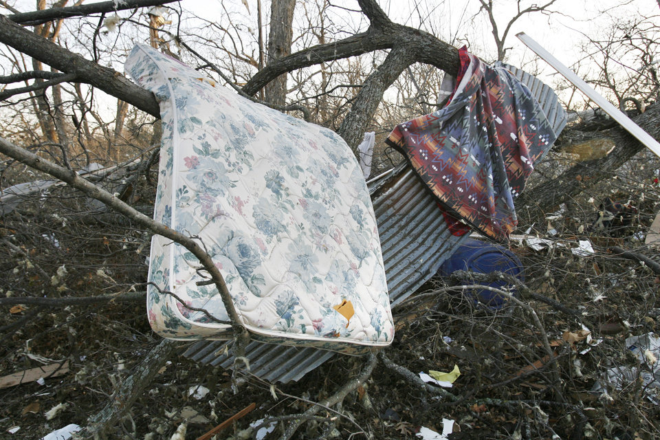 Photo - The bed from a home rests in a tree behind a residence on Highway 70 after Tuesday's deadly tornado in  Lone Grove, Okla., on Wednesday, Feb. 11, 2009.   Photo by Steve Sisney, The Oklahoman