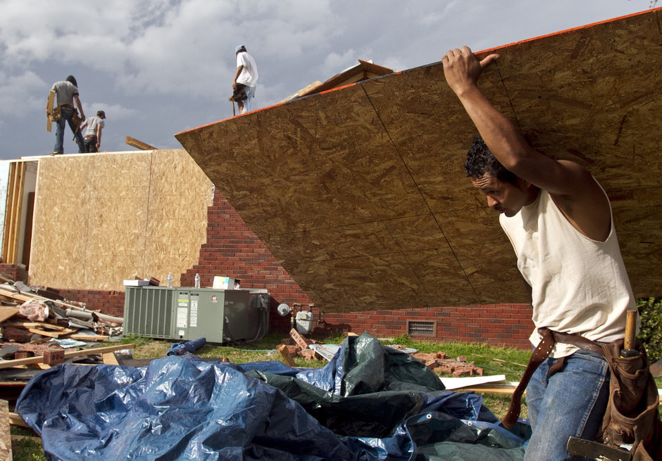 Workers try to board up a home that was damaged after a tornado left a path of destruction as it passed through Friday, March 2, 2012, in Athens, Ala. Powerful storms stretching from the Gulf Coast to the Great Lakes flattened buildings in several states, wrecked two Indiana towns and bred anxiety across a wide swath of the country in the second powerful tornado outbreak this week.  (AP Photo/Butch Dill) ORG XMIT: ALBD113