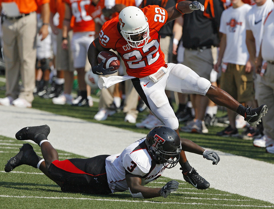 Photo - Oklahoma State's Dantrell Savage (22) is knocked out of bounds by Texas Tech's Jamar Wall (3) during the first half of the college football game between the Oklahoma State University Cowboys (OSU) and the Texas Tech University Red Raiders (TTU) at Boone Pickens Stadium  on Saturday, Sept. 22, 2007, in Stillwater, Okla. 