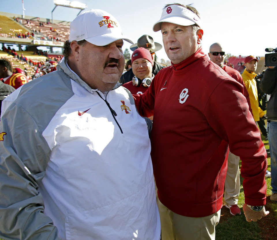 Photo - Oklahoma coach Bob Stoops talks with Iowa State offensive coordinator Mark Mangino after a college football game between the University of Oklahoma Sooners (OU) and the Iowa State Cyclones (ISU) at Jack Trice Stadium in Ames, Iowa, Saturday, Nov. 1, 2014. Photo by Bryan Terry, The Oklahoman