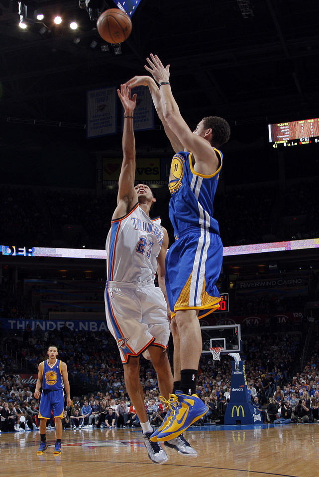 Golden State's Klay Thompson (11) shoots over Oklahoma City 's Kevin Martin (23) during an NBA basketball game between the Oklahoma City Thunder and the Golden State Warriors at Chesapeake Energy Arena in Oklahoma City, Sunday, Nov. 18, 2012.  Photo by Garett Fisbeck, The Oklahoman