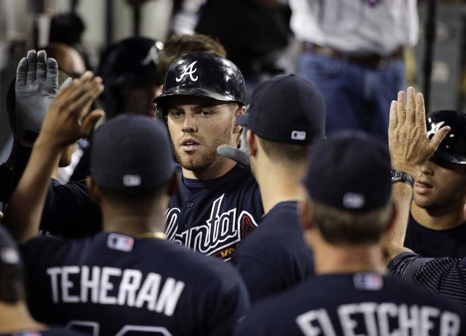 Photo - Atlanta Braves' Freddie Freeman, center, is congratulated by teammates after hitting a two-run home run during the third inning of a baseball game against the Los Angeles Dodgers on Tuesday, July 29, 2014, in Los Angeles. (AP Photo/Jae C. Hong)