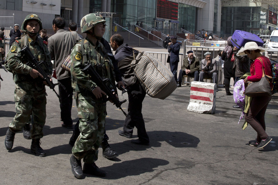 Photo - Heavily armed Chinese paramilitary policemen march past the site of the Wednesday's explosion outside the Urumqi South Railway Station in Urumqi in northwest China's Xinjiang Uygur Autonomous Region Thursday, May 1, 2014. Chinese President Xi Jinping has demanded