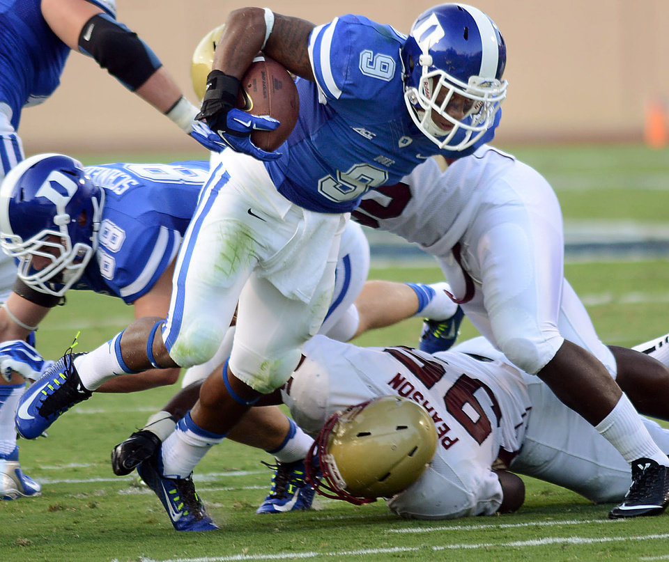 Photo - Duke's Josh Snead (9) runs past Elon's Michael Pearson (95) during an NCAA college football game Saturday, Aug. 30, 2014, in Durham, N.C.  (AP Photo/The Herald-Sun, Bernard Thomas)