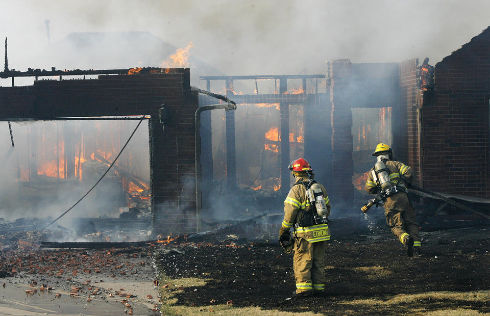 Firefighters spray water on a house destroyed by wildfires in Midwest City,  Thursday, April 9, 2009. This home is on Village Ave. in Oakwood East Royale addition.  Photo by Jim Beckel, The Oklahoman