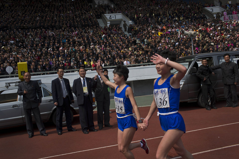 Photo - North Korean twin sisters Kim Hye Gyong (135) and Kim Hye Song (136) take a victory lap together inside Kim Il Sung Stadium after placing first and second respectively in the the women's Mangyongdae Prize International Marathon in Pyongyang, North Korea on Sunday, April 13, 2014. The annual race, which includes a full marathon, a half marathon, and a 10-kilometer run, was open to foreign tourists for the first time this year. (AP Photo/David Guttenfelder)