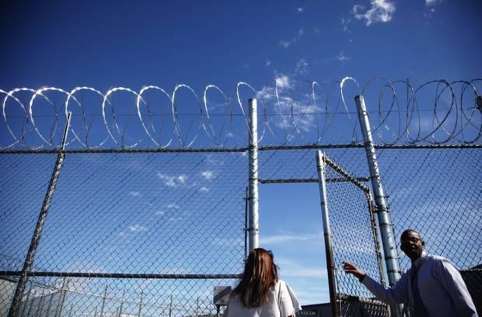Photo - Sheila Devereux walks through a gate opened by Unit Manager Shola Shopeyin at the Oklahoma Department of Corrections in McLoud, Okla. Devereux was sentenced to life in prison without parole after her third felony drug conviction. Devereux's case was handled by two of the Tulsa police officers who, in 2010, were under investigation for police corruption. ADAM WISNESKI/Tulsa World