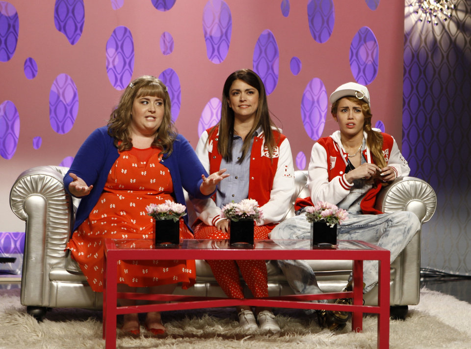 Photo - This Oct. 5, 2013 photo released by NBC shows, from left, Aidy Bryant, Cecily Strong, and guest host Miley Cyrus in a scene from the late-night comedy series