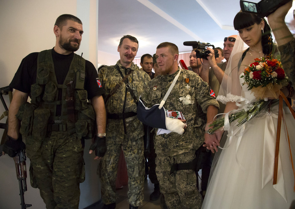 Photo - Igor Strelkov, a pro-Russian separatist commander, 2nd left, attends the wedding ceremony of platoon commander Arsen Pavlov, also known as Motorola, and Elena Kolenkina in the city of Donetsk, eastern Ukraine Friday July 11, 2014. (AP Photo/Dmitry Lovetsky)