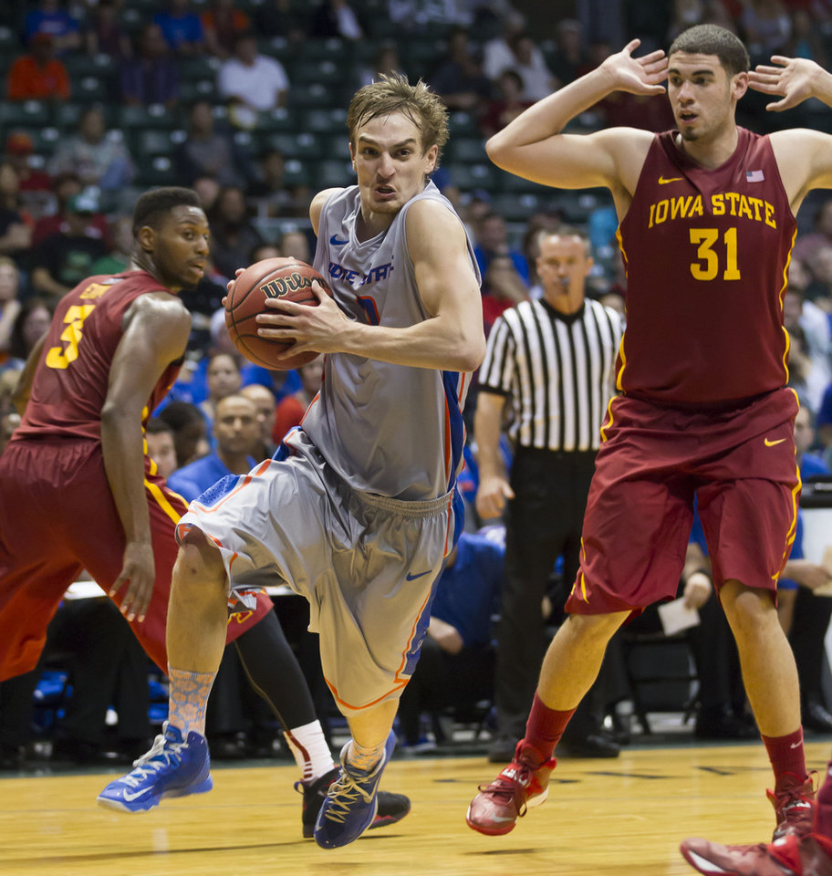 Photo - Boise State guard Anthony Drmic, center, drives the baseline as Iowa State forward Melvin Ejim (3) and forward Georges Niang (31) watch during the second half of an NCAA college basketball game at the Diamond Head Classic on Wednesday, Dec. 25, 2013, in Honolulu. Iowa State won 70-66. (AP Photo/Eugene Tanner)