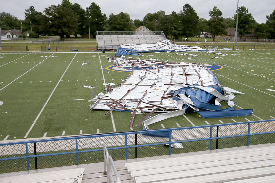 Photo - Pieces from the roof of a gymnasium at Choctaw Middle School litter the school's football field after high winds from a storm caused damage in Choctaw, Okla.,, Tuesday, Aug. 27, 2019. [Bryan Terry/The Oklahoman]