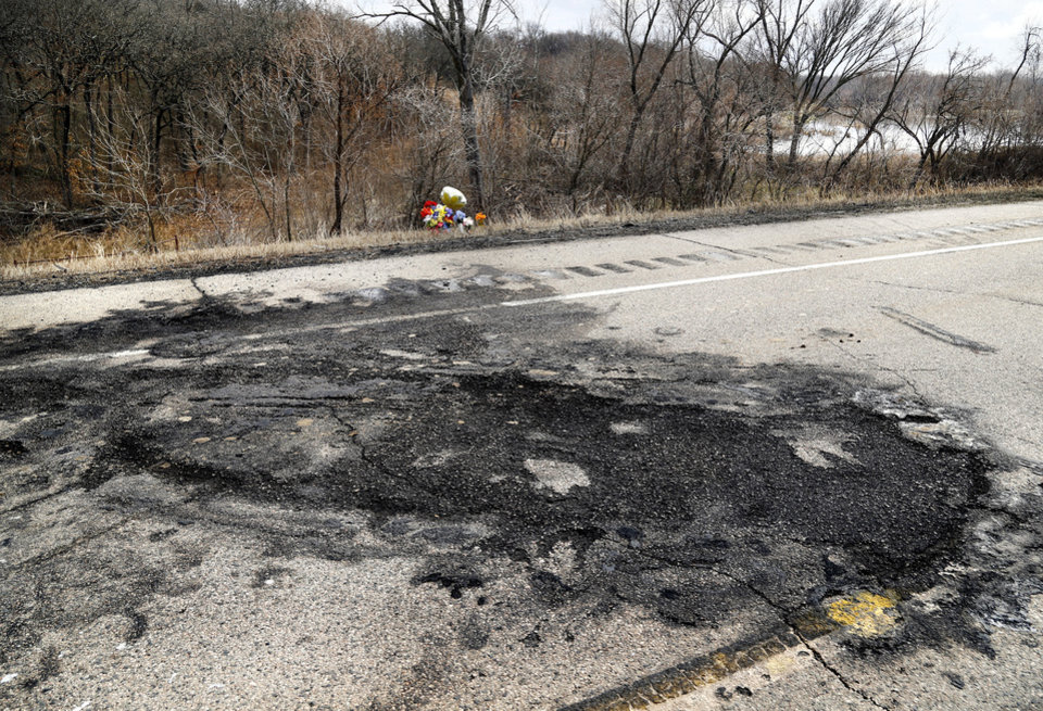 Photo - Flowers and a balloon bouquet were placed on the shoulder of a two-lane highway  near a blackened and charred section of asphalt on SH 377 Monday, March 11, 2019, where three people died in a crash last week. Konawa Middle School athlete Rhindi Kay Isaacs, 12, was among three people who died in a fiery, head-on collision Friday evening. The Konawa Public School District said six students from the  junior high school girls softball team were aboard the bus  traveling home at the time of the crash. The team's coach was driving the bus when it was struck by an SUV on SH 377, between Bowlegs and Konawa, in Seminole County. The Oklahoma Highway Patrol said the SUV was traveling in the northbound lane just after 7 p.m. when it swerved and collided with a Konawa School activity bus after the driver of the SUV swerved when passing another vehicle, 