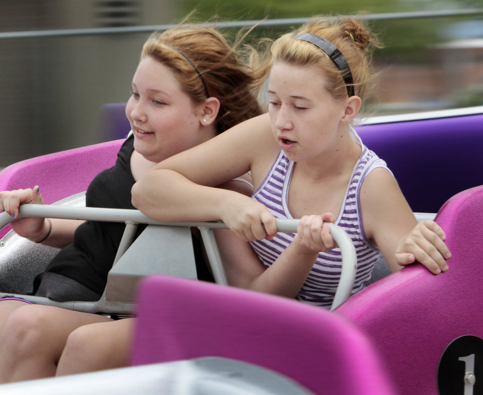 Photo - Hailee Butts (left) and cousin Kaylee Butts, both 14, ride the Sizzler at the Lions Club Carnival on Saturday, April 28, 2012, in Norman, Okla.  Photo by Steve Sisney, The Oklahoman