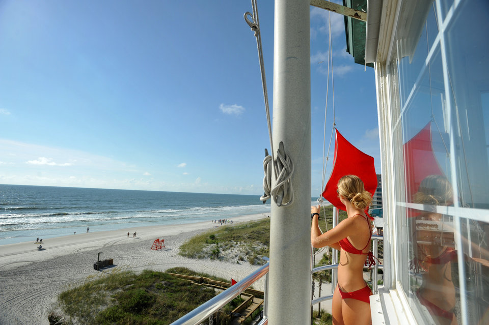 Photo - Lifeguard Gabrielle Porter raises flags, including the red high hazard flag, Tuesday morning, July 1, 2014, at the Red Cross lifeguard station in Jacksonville Beach, Fla. The red flag was raised in anticipation of rip currents and high waves from a tropical depression forming off Florida's coast that is expected to become Tropical Storm Arthur and pass to the east of Florida. (AP Photo/The Florida Times-Union, Will Dickey)