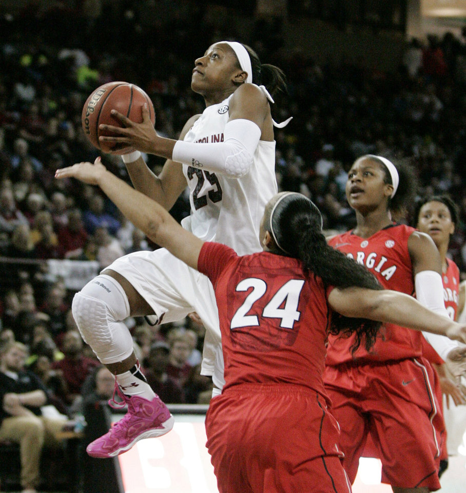 Photo - South Carolina's Tiffany Mitchell (25) drives for the basket as Georgia's Marjorie Butler (24) defends during the first half of an NCAA college basketball game Thursday, Feb. 27, 2014, in Columbia, S.C. (AP Photo/Mary Ann Chastain)
