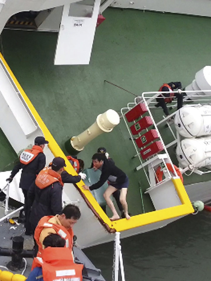 Photo - In this April 16, 2014 photo released by South Korea Coast Guard via Yonhap News Agency, South Korean coast guard officers rescue South Korean ferry Sewol Capt. Lee Joon-seok, wearing a sweater and underwear, from the sinking ferry in the water off the southern coast near Jindo, South Korea. Prosecutors indicted the captain of the sunken ferry and three crew members on homicide charges Thursday, May 15, alleging they were negligent and failed to protect more than 300 people missing or dead in the disaster. Less serious indictments were issued against the 11 other crew members responsible for navigating the vessel. (AP Photo/South Korea Coast Guard via Yonhap) KOREA OUT