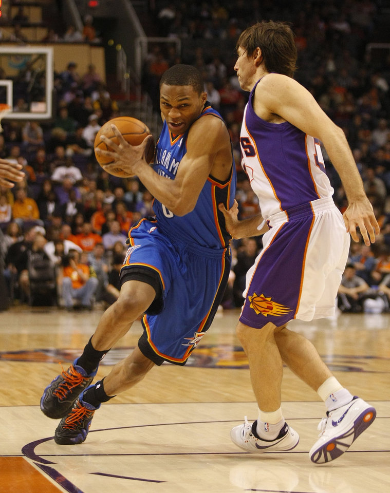 Photo - Oklahoma City Thunder's Russell Westbrook, left, drives on Phoenix Suns' Steve Nash during the first quarter of an NBA basketball game on Wednesday, Dec. 23, 2009, in Phoenix.  (AP Photo/Rick Scuteri)  ORG XMIT: AZRS101