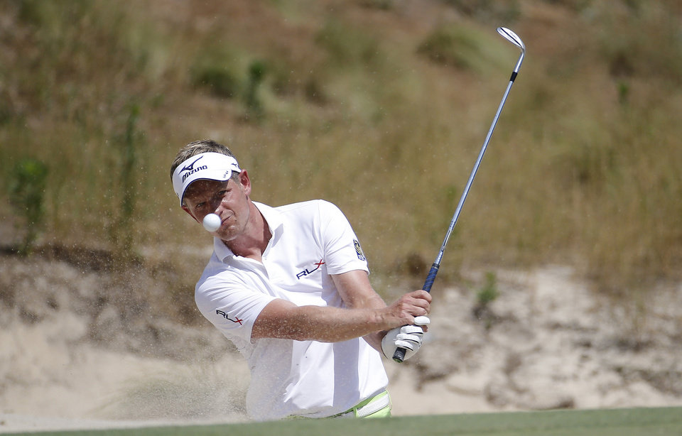 Photo - Luke Donald, of England, hits out of the bunker on the 16th hole during a practice round for the U.S. Open golf tournament in Pinehurst, N.C., Wednesday, June 11, 2014. The tournament starts Thursday. (AP Photo/Matt York)