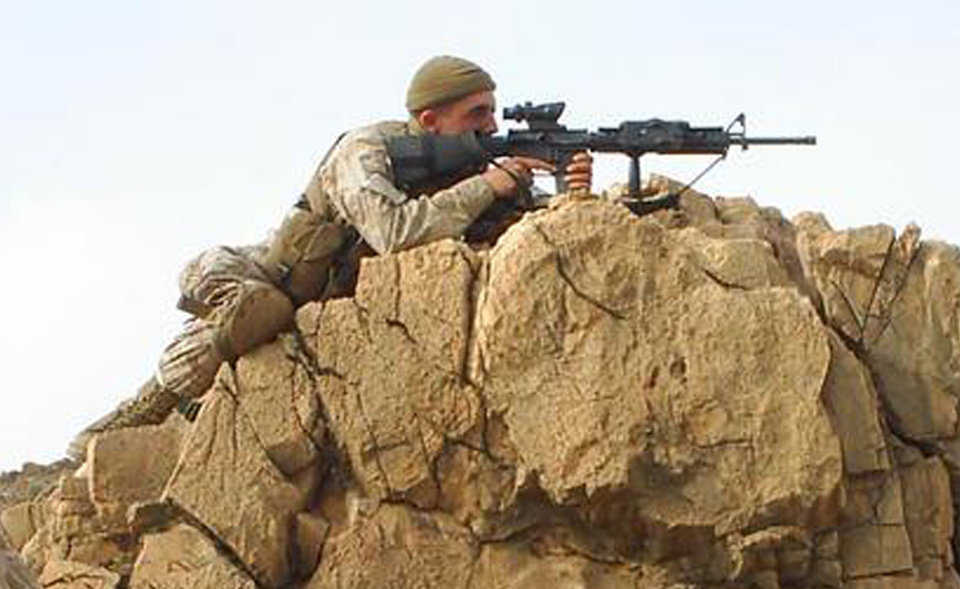 This Feb. 2006 photo provided by Josh Echeverria shows U.S. Marine Garrett Anderson in a prone firing position in Kunar Province, Afghanistan. Anderson, an ex-Marine filmmaker whose unit carried pocket digital cameras into some of the worst fighting in Iraq is using that footage, and post-war interviews, to open viewers' eyes about combat and help himself deal with the lasting emotional impact. (AP Photo/Josh Echeverria)