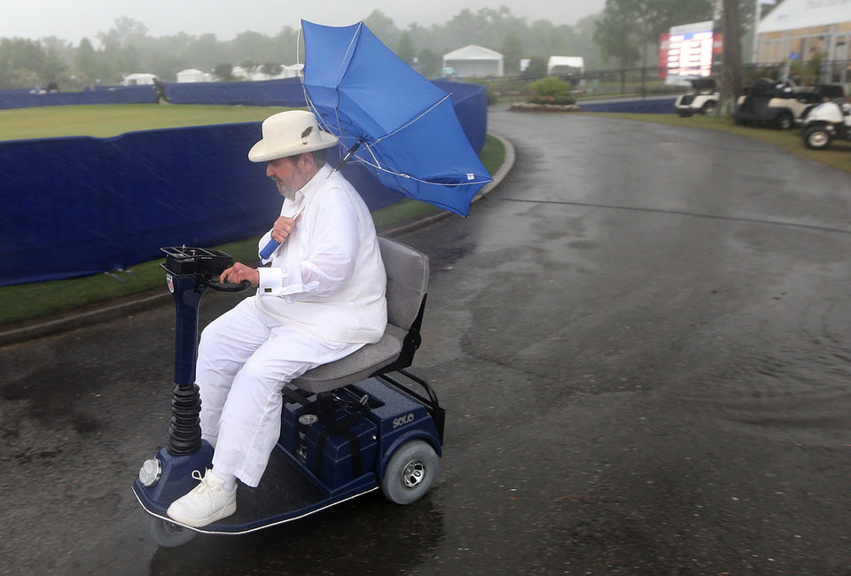 Chef Paul Prudhomme heads to the clubhouse as officials order the evacuation of all temporary structures following the issuing of a tornado warning during the Zurich Classic Pro-Am at the TPC Louisiana on Wednesday, April 24 , 2013 in Avondale, La..  (AP Photo/The Times-Picayune, Michael DeMocker) MAGS OUT; NO SALES; USA TODAY OUT; THE BATON ROUGE ADVOCATE OUT