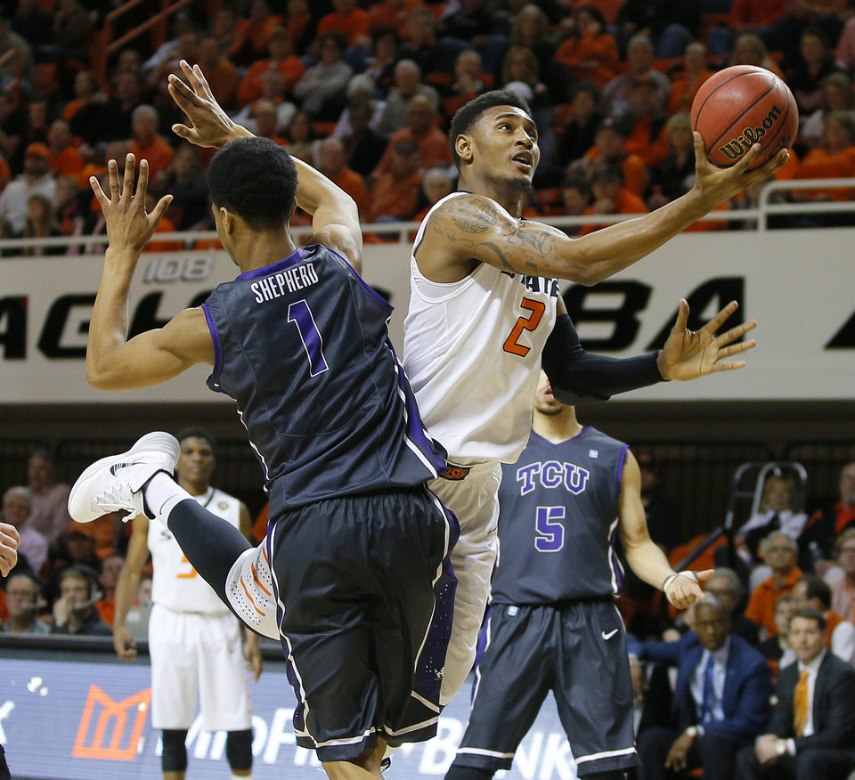 Photo - Oklahoma State's Le'Bryan Nash (2) goes past TCU's Karviar Shepherd (1) during an NCAA college basketball game between Oklahoma State University (OSU) and TCU at Gallagher-Iba Arena in Stillwater, Okla., Wednesday, Jan. 15, 2014. Oklahoma State won 82-50. Photo by Bryan Terry, The Oklahoman