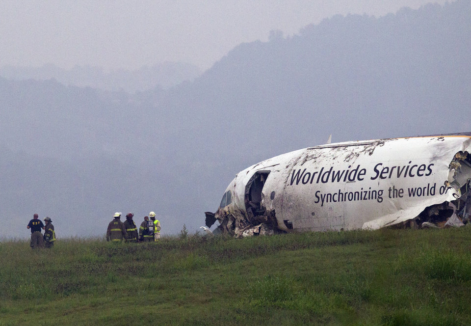 Photo - FILE - In this Aug. 14, 2013, file photo, fire crews work the scene of a UPS cargo plane crash at the Birmingham-Shuttlesworth International airport in Birmingham, Ala. Federal investigators are looking at pilot fatigue, among other issues, as a possible factor in the fatal predawn crash of a UPS cargo jet. The National Transportation Safety Board scheduled a hearing for Feb. 20, 2014, on the accident, which killed both pilots.(AP Photo/Butch Dill, File)