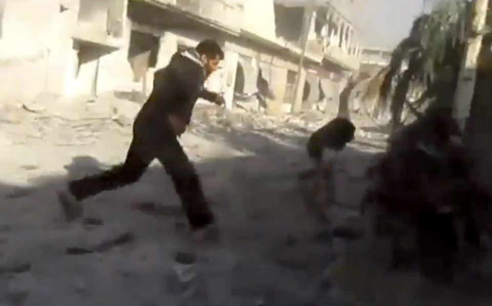 Photo -   This image taken from video obtained from Shaam News Network, which has been authenticated based on its contents and other AP reporting, men running during heavy bombing from military warplanes in Houla, Syria, Tuesday, Nov. 6, 2012. The Britain-based Syrian Observatory for Human Rights said air raids on Houla, a group of villages in central province of Homs, killed several people.(AP Photo/Shaam News Network via AP video)